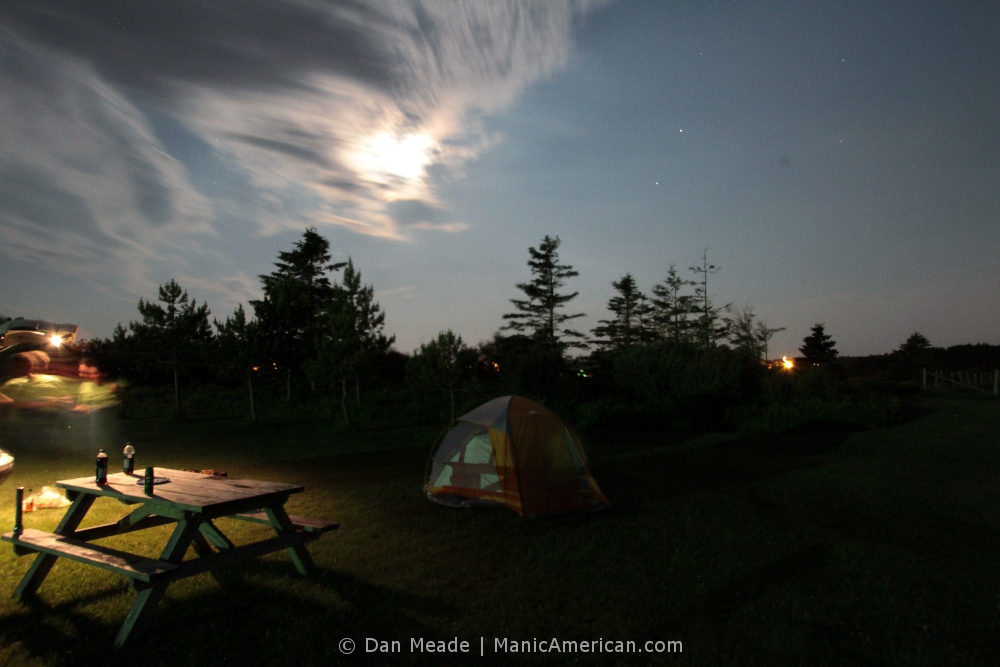 A tent illuminated by moonlight and flashlight. Several bottles stand on a nearby bench. & Dan Meade: Night Exposure / The Manic American